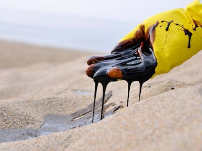 A gloved hand of unidentifiable/unnamed emergency worker scooping oil from pristine beach sand.